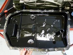 BMW 320d 2009 stará olejová vaňa s integrovaným filtrom na automatickú prevodovku počas výmeny oleja a filtra